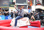 Sarah Haines cheers on Michael Strahan riding a Mechanical Bull during a Good Morning America filming promoting PBR: Unleash the Beast in Times Square on January 4, 2019 in New York City.