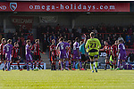 Home team's midfielder Alex Kenyon is shown a straight red card for a foul on Carl McHugh as Morecambe (in red stripes) hosted Plymouth Argyle in a League 2 fixture at the Globe Arena. The stadium was opened in 2010 and replaced Morecambe's traditional home of Christie Park which had been their home since 1921, the year after their foundation. Plymouth won this fixture by 2-0 watched by 2,081 spectators, in a game delayed by 30 minutes due to traffic congestion affecting travelling Argyle fans.