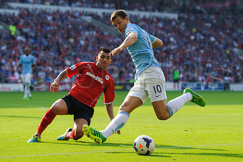 25.08.2013 Cardiff, Wales. Man City Forward Edin Dzeko is challenged by Cardiff Midfielder Gary Medel during the second half of the Barclays Premier League football match between Cardiff City and Manchester City at Cardiff City Stadium.