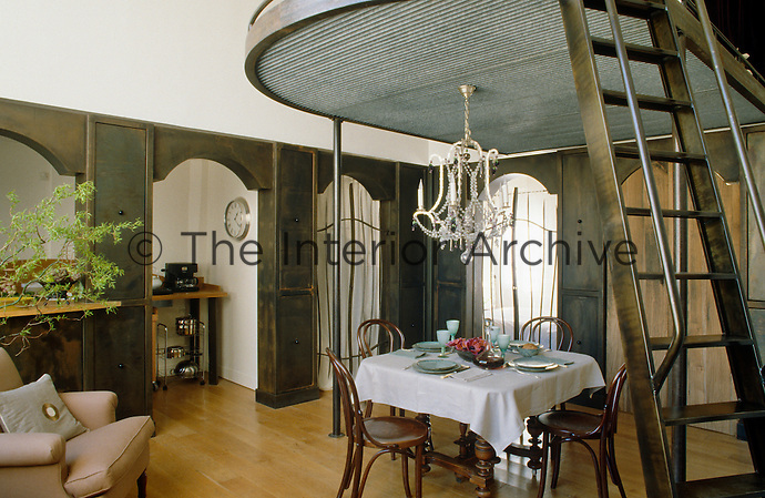 In an open-plan living/dining room a compact dining area is situated under a curved steel mezzanine floor from which an antique chandelier has been suspended