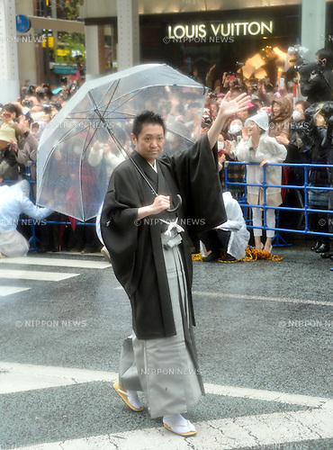 March 27, 2013, Tokyo, Japan - Onoe Shoroku waves to fans as some 60 leading Kabuki actors parade in the rain through the main street of Tokyo's Ginza shopping district on Wednesday, March 27, 2013, in celebration of the grand opening of new Kabuki theater. After three years of renovation, the majestic theater for Japan's centuries-old performing arts of Kabuki will open its doors to the public with a three-month series of most sought-after plays.  (Photo by Natsuki Sakai/AFLO)