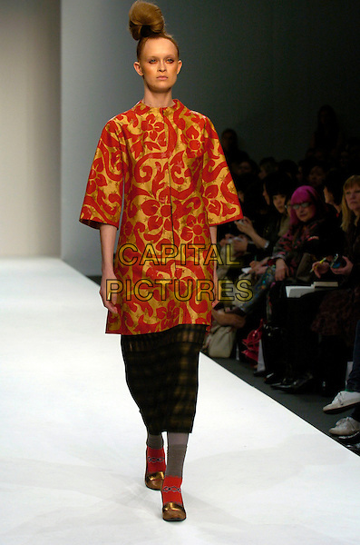 MODEL.At the Eley Kishimoto a/w 2007/8 Catwalk Show during London Fashion Week, BFC Tent, London, England, February 16th 2007..full length runway modelling hair red and gold patterned tunic dress.CAP/CAN.©Can Nguyen/Capital Pictures