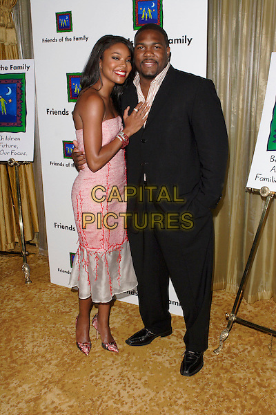 GABRIELLE UNION & HUSBAND.The 9th Annual Family Matters Benefit and Celebration held at the Regent Beverly Wilshire Hotel, Beverly Hills, Los Angeles, California, USA, 3 June 2005..full length pink dress married wife.Ref: ADM.www.capitalpictures.com.sales@capitalpictures.com.©AdMedia/Capital Pictures.