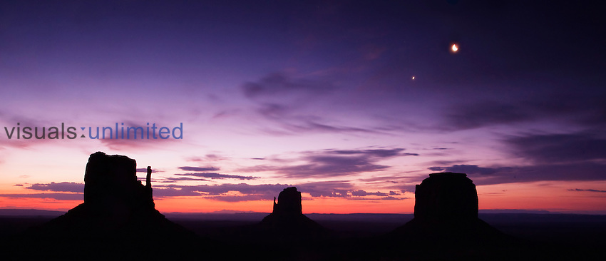 Monument Valley on the Navajo Indian Reservation showing East Mitten, West Mitten, and Merrick Butte at sunrise.