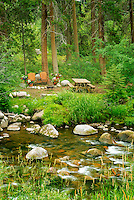 Picnic site with table chairs and flowers along Gore Creek. Vail, Colorado