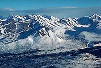 Aerial view of snow-covered peaks of Alaska Range and Turnagain Arm, Pacific Ocean.