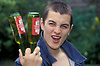 16 year old boy showing off with two bottles of lager UK. Posed by model