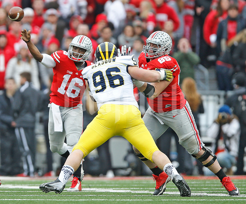 Ohio State Buckeyes quarterback J.T. Barrett (16) gets a pass off as Ohio State Buckeyes offensive lineman Pat Elflein (65) and Michigan Wolverines defensive lineman Ryan Glasgow (96) battle at Ohio Stadium on November 29, 2014. (Chris Russell/Dispatch Photo)
