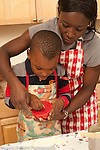 4 year old boy in kitchen with his mother learning to cook traditional cornmeal dish from Togo, setting hand timer