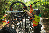 NWA Democrat-Gazette/BEN GOFF @NWABENGOFF<br /> Garrett Hubbard of Bentonville, with the Gravitas mountain bike team, loads his bike for the shuttle ride back to the top Thursday, June 14, 2018, during a grand opening for new downhill mountain bike trails at Lake Leatherwood City Park in Eureka Springs. The Walton Family Foundation and Eureka Springs Parks and Recreation Commission partnered to build the new downhills trails at the park already known for it's extensive network of singletrack. Many of the new trails, built by Rock Solid Trail Contracting, include large, expert-level drops, jumps and technical rock features. Over the next 60 days, the Eureka Springs Parks and Recreation Commission will be funding free shuttles operated by Adventure Mountain Outfitters and Phat Tire Bike Shop for riders on most Thursdays and Fridays. Justin Huss, director of the commission, advises visitors to call the park to check on shuttle schedules before visiting. Huss says after the initial 60 days, the shuttle services will be offered on busy days with the purchase of a pass.