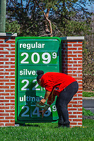 Worker places new price letting on the sign at the BP station at Cleveland and Main in Westerville, Ohio.