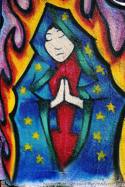 An image of the Virgin of Guadalupe appears to be calm and impervious to the flames on a wallnear a Santa Fe Tatooo shop.