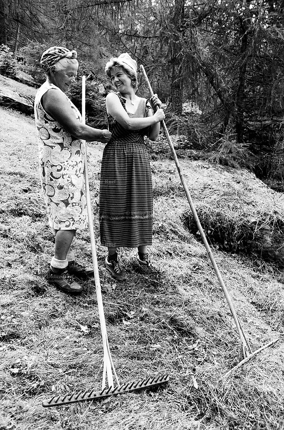 Switzerland. Canton Graubunden. Alp Bratel, 600 meters above Bondo. Bregaglia valley. Family Salis makes hay on the grassland. Mother and daughter with their rakes. Swiss alpine farmers. Alps mountains peasants.  © 1994 Didier Ruef