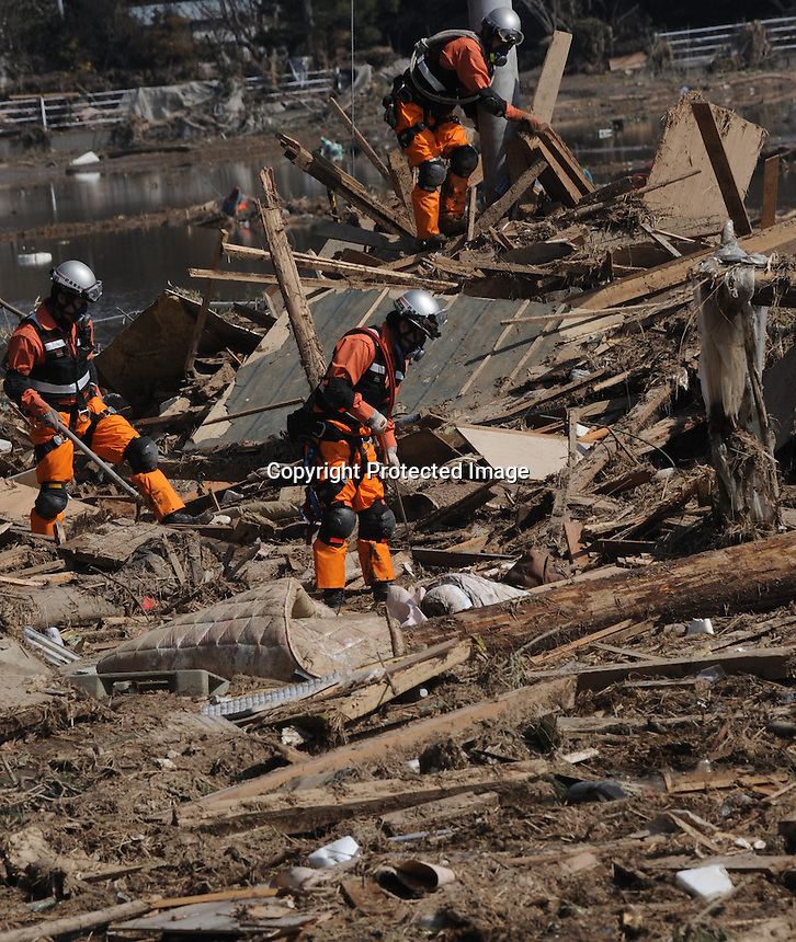 Search and rescue teams look through the remains of houses in the devasted  town of Natori, after the Tsunami devastated the entire pacifc coastline of Japan after the earthquake and tsunami devastated the area Sendai, Japan.<br />