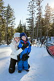 USA, Oregon, Bend, a mom and son smile for a photo before heading out for their sled dog ride at Mt. Bachelor