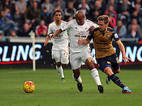 (L-R) Andre Ayew of Swansea challenged by Nacho Monreal of Arsenal during the Barclays Premier League match between Swansea City and Arsenal at the Liberty Stadium, Swansea on October 31st 2015