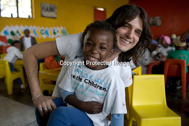 ALEXANDRA, SOUTH AFRICA - SEPTEMBER 2: Taylor Locke (the lead guitarist in the band Rooney) interacts with children at Hlayisanani Pre-School on September 2, 2008 in Alexandra, outside Johannesburg, South Africa. Mischa Barton spent 2 days visiting Save The Children supported projects in South Africa, meeting school children and young children. Save The Children are helping about 51,000 children made by HIV/AIDS and poverty to access food, healthcare, social security and education. (Photo by Per-Anders Pettersson/Getty Images For Save The Children).