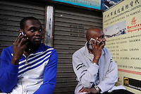 CHINA Guangzhou , african trader buy  textiles in export- and wholesale markets which the ship to Africa for their shops, Nigerians making deals by phone / CHINA , Provinz Guangdong , Metropole Guangzhou (Kanton) , Haendler aus Afrika kaufen in Grosshandels-/Exportmaerkten Textilien fuer Ihre Laeden in Afrika ein, Nigerianer mit Mobiltelefon