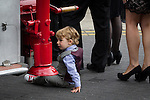 © Joel Goodman - 07973 332324 . 02/09/2013 . Bury , UK . A boy falls over at the back of the vintage fire engine used to carry Stephen Hunt's coffin , as mourners enter the church . The funeral of fireman Stephen Hunt at Bury Parish Church today (Tuesday 3rd September 2013) . Stephen Hunt died whilst tackling a blaze at Paul's Hair World in Manchester City Centre in July 2013 . Photo credit : Joel Goodman
