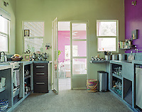 In this kitchen simple cupboards and work surfaces have been constructed in cool grey concrete with one wall painted a vivid contrasting purple