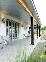 Glass doors open onto a long porch supported by a series of steel girders and dotted with white canvas garden chairs