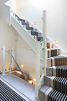 A striped stair runner, lit by ankle level wall lights, connects two flights of stairs in this mews house