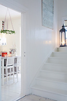 Original wood cladding on the staircase wall has been exposed and restored with a clean, varnished layer of white paint