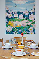An Andoo kitchen table by Walter Knoll is laid for lunch. The painting behind is The Dream by Olga Vujadinovic