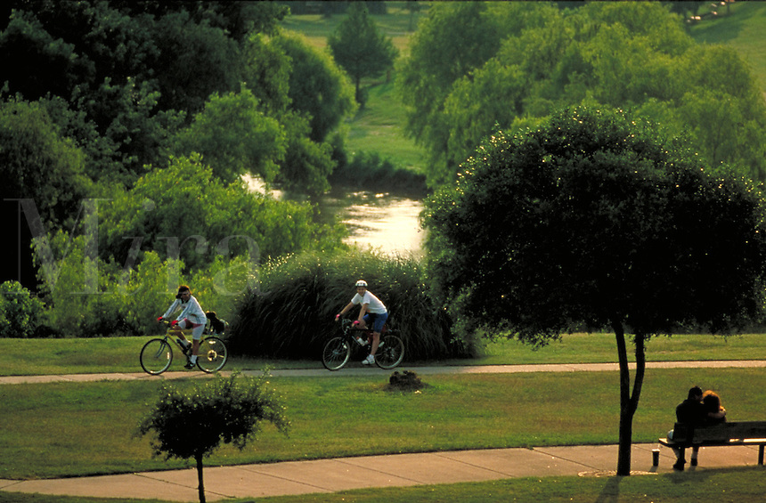 Couples enjoying bayou trail. One couple sits on a park bench while bicyclists ride by on a bike path. Houston Texas, Buffalo Bayou.