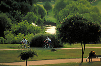 Couples enjoying bayou trail. One couple sits on a park bench while bicyclists ride by on a bike path. Houston Texas, Buffalo Bayou.