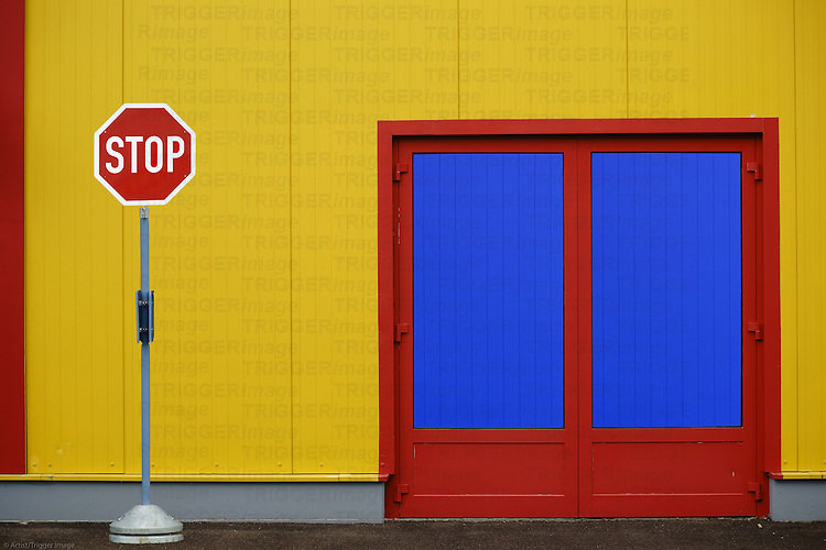A colorful and striking sidewall of a shopping center with a side entrance and a stop sign.