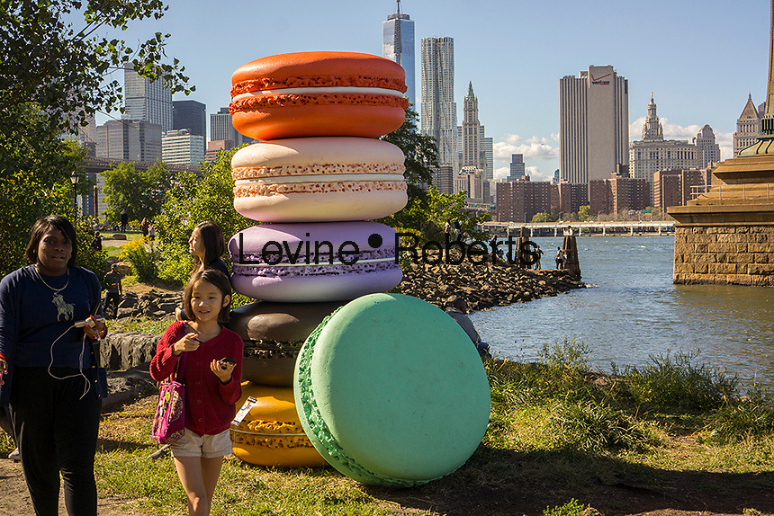 "Visitors to the Brooklyn neighborhood of Dumbo pass ""Macaron"" by the artist Daisuke Kiyomiya during the annual Art Under the Bridge Dumbo Arts Festival on Saturday, September 28, 2013.  Dumbo has been a neighborhood shared by industry and artists but high real estate prices have created opportunities for development with the subsequent increase in rents.  (© Richard B. Levine)"