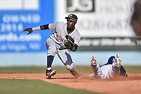 Charleston RiverDogs shortstop Jorge Mateo (2) fields and attempts to apply the tag as Emerson Jimenez (14) slides in safely during a game against the Asheville Tourists on June 13, 2015 in Asheville, North Carolina. The Tourists defeated the RiverDogs 10-6. (Tony Farlow/Four Seam Images)
