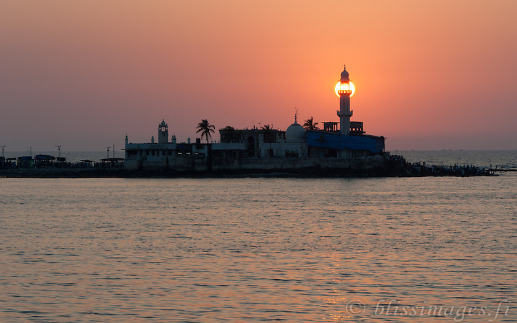 The setting sun makes a lighthouse of the ancient minaret of the Haji Ali Mosque, just offshore Mumbai, India in the Arabian Sea.
