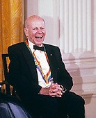 Composer William Schuman listens as first lady Barbara Bush makes remarks during a ceremony for 1989 Kennedy Center Honorees in the East Room of the White House, December 3, 1989 in Washington, DC. The 1989 honorees are: actress and singer Mary Martin, dancer Alexandra Danilova, singer and actor Harry Belafonte, actress Claudette Colbert, and composer William Schuman.<br /> Credit: Peter Heimsath / Pool via CNP