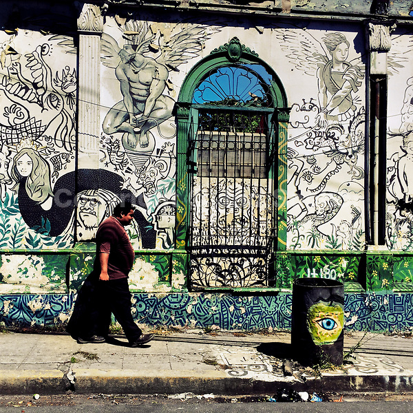 A Salvadoran man walks in front of a ruined house with Spanish colonial architecture elements, painted over by a local artist, in the center of San Salvador, El Salvador, 12 November 2016.