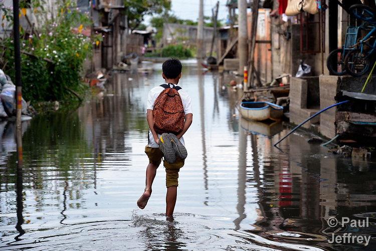 A boys walks down a flooded street in Biñan, Laguna, in the Philippines. Residents here have been subjected to increased flooding from the Laguna de Bay in recent years, and with the help of the ACT Alliance are organizing to look for alternatives.
