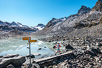 Crossing a bridge while running near the Lac du Grand Désert during the Via Valais, a multi-day trail running tour connecting Verbier with Zermatt, Switzerland.