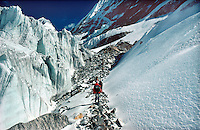 .High-altitude trekking group ascend a rock corridor through the Drolambo Glacier, below the Tesi Lapcha pass, Rolwaling region, Nepal Himalaya...