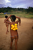 Roraima, Brazil. Yanomami Indian girls with yellow forest fruits.