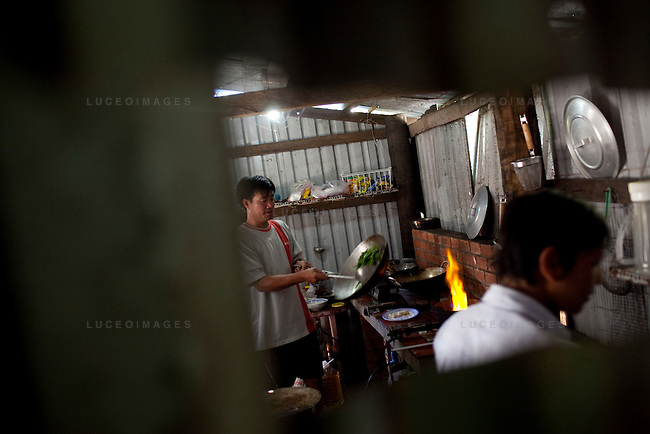 Dao Van Dan, 38, left, owner of the Orchid Restaurant, cooks for tourists on Con Son Island, part of the Con Dao Islands.The 16 mountainous islands and islets are situated about 143 miles southeast of Ho Chi Minh City in Vietnam, in the South China. Photo taken Thursday, May 6, 2010...Kevin German / LUCEO For the New York Times