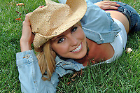Closeup of a teenage girl with a big smile wearing a straw cowboy hat, white top, and a blue jacket lays on grass.