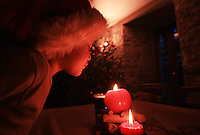 La Canourgue,France : Thomas Fourcaulx, 4 plays with Christmas candle in their home , in the mountains of La Canourgue district of Lozere in south of France on Dezember 24, 2013 -  (Photo by Paulo Amorim)