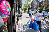 NEW YORK, NY - MAY 10: A man with a face mask crosses the front of a store carrying flowers in his hands in Jackson Heights on Mother's Day on May 10, 2020 in Queens, New York. COVID-19 has spread to most countries in the world, claiming more than 283,000 lives and more than 4.1 million people infected, Queens has been one of the places most affected by the Coronavirus. (Photo by Pablo Monsalve / VIEWpress via Getty Images)