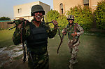 Iraqi National Policemen smile and dance with pleasure after discovery a stash of linked machine-gun ammunition during a raid on a mosque in the Baghdad Sunni neighborhood of Ghazaliyah  on Friday August 18, 2006.  The raid, which yielded weapons and IED making materials, was part of an operation by bolstered US and Iraqi forces in the hopes of getting a handle on the extraordinary numbers of sectarian killings in Baghdad.