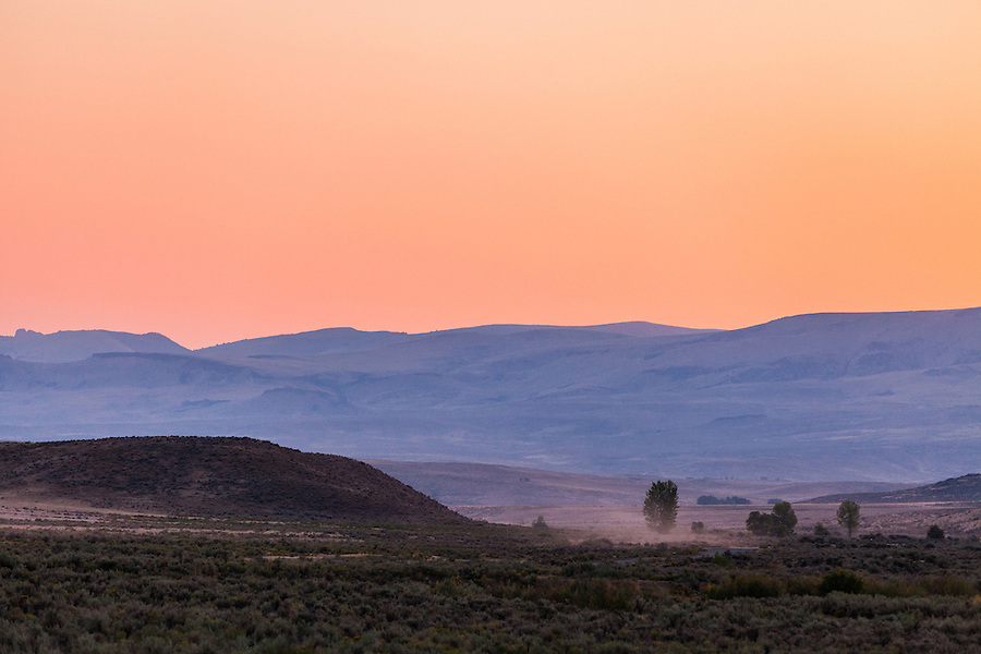 The sunset bathes the sky in an orange-red glow and distant hills in a purplish pastel hue in this quiet remote place in Southeast Oregon.