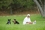Ted Cooley with three dogs relaxing in Spring grass.