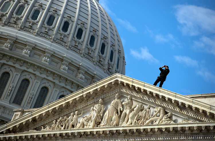 UNITED STATES - OCTOBER 01: A Capitol Police officer looks out over the east front of the Capitol. (Photo By Tom Williams/CQ Roll Call)