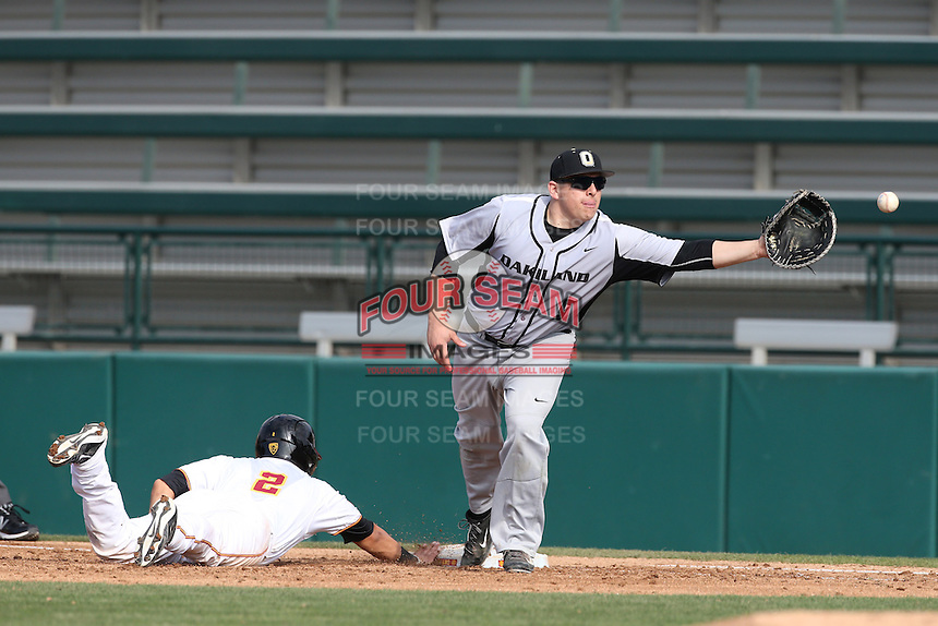 Zach Sterry (5) of the Oakland Grizzlies reaches for the throw as Jeremy Martinez (2) of the Southern California Trojans slides back to first base during a game at Dedeaux Field on February 21, 2015 in Los Angeles, California. Southern California defeated Oakland, 11-1. (Larry Goren/Four Seam Images)
