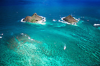 An aerial shot of the Mokulua Islands and visible reef off of Lanikai, O'ahu; kayakers make their way towards the left island while a nearby boat creates a wake away from the same.